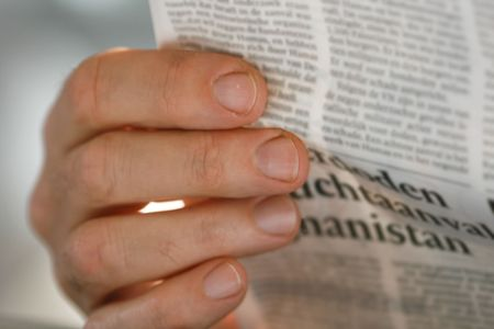unrecognizable: male hand holding newspaper Stock Photo