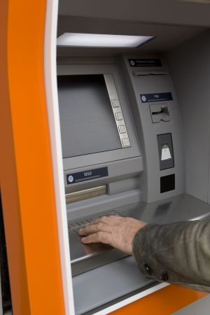 Male hand pushing digits on ATM  photo