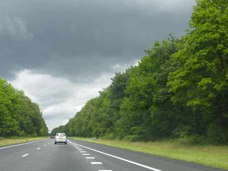 Car driving with sun at the back towards very dark ominous clouds Stock Photo - 5106253