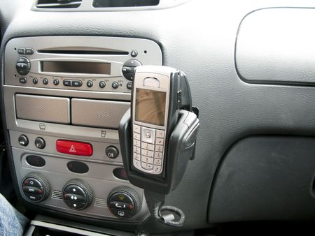 reversing: Console of car showing  mobile phone hands free car kit, radio and controls.