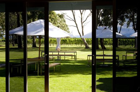 Picnic tables seen through sliding doors in sunny vineyard photo