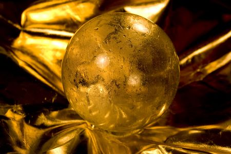Golden crystal ball on golden background. What will the new year bring concept. photo