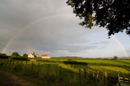 the setting sun: Huge rainbow above farmland with farm in setting sun