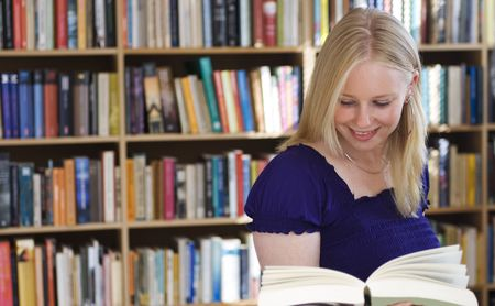 Attractive blonde girl smiles while reading a book in front of bookshelves photo