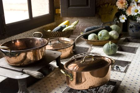 Copper pans on 17th century coal stove in preserved kitchen in an old chateau in Burgundy, France. Looks like a Dutch painted still life with fruit and natural light. photo