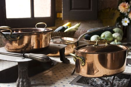 17th: Copper pans on 17th century coal stove in preserved kitchen in an old chateau in Burgundy, France. Still life with fruit and natural light. Stock Photo