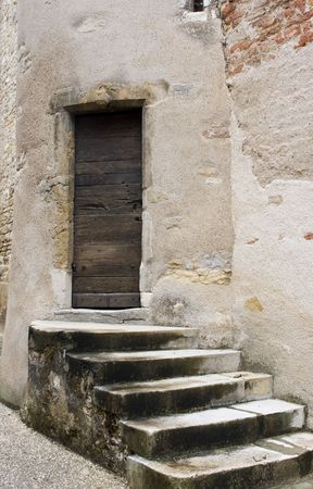 stone stairs: Five weathered stone steps to an old wooden front door in a french town
