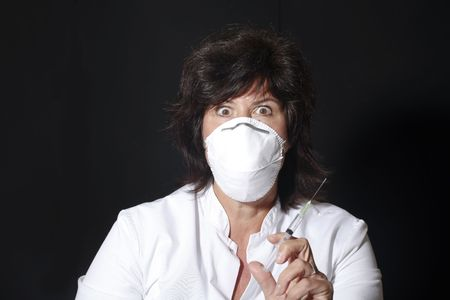 Female doctor with syringe and mouthcap looking frightening photo