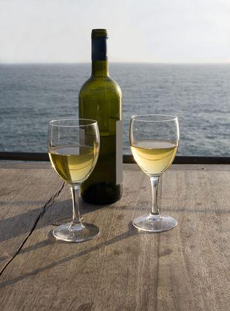 木桌上放着两杯白葡萄酒和一瓶酒,窗外是夕阳西下的大海