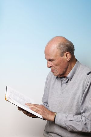 xxxl: Healthy looking 84 year old male in grey pullover reading dictionary on blue background (XXXL)