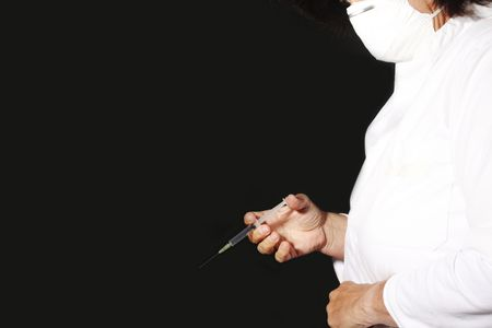 Doctor with surgical mask and syringe photo