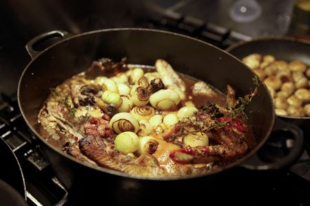 au: Traditional French chicken casserole, coq au vin. Button mushrooms, bacon, shallots, thyme and a red wine sauce in a big black casserole pan. Mushrooms in other pan.  Stock Photo