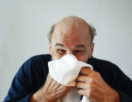 80+ year old senior sneezing in cotton handkerchief photo