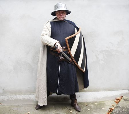 buckler: Middle aged male in traditional medieval soldier clothing with shield and sword