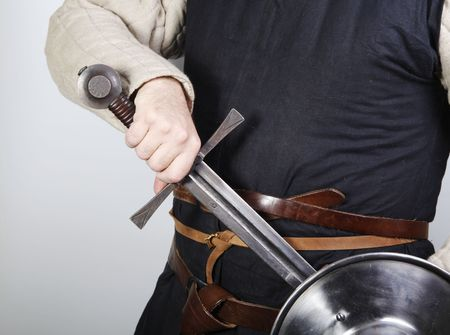 buckler: Unsheating a sword in traditional  medieval costume.  Stock Photo