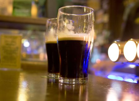 Two half full stout beers on a bar