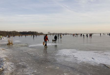 A typical icy sunday in the Netherlands. People walking, skating and playing on the ice. Stock Photo - 6092106
