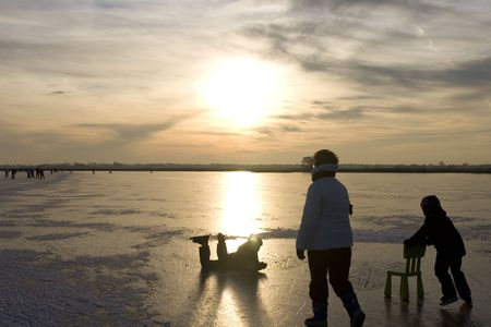 Frozen lake with sunset in the Netherlands. Children learnig to skate with the typical Dutch chair education Stock Photo - 6092167