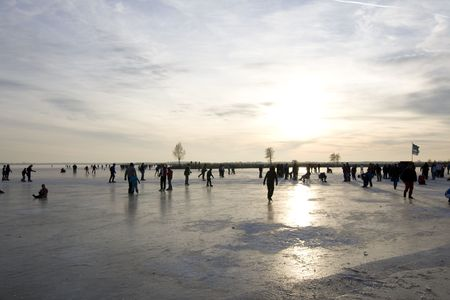A frozen lake in the Netherlands with people skating Stock Photo - 6092053