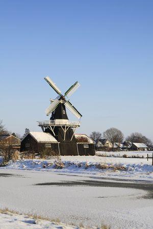 boer: Antiguo molino de madera y grano desde 1903 (renovado en 1985) en diez Boer, Holanda cerca de un r�o congelado   Foto de archivo