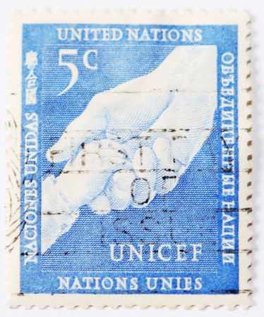 unicef: USA-circa : Postage stamp of Unicef with childs hand in hand of adult.The United Nations Childrens Fund (or UNICEF) was created by the United Nations General Assembly on December 11, 1946 to provide emergency food and healthcare to children in countries