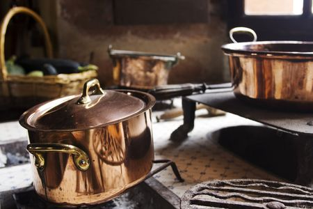 17th: Antique copper pans on 17th century coal stove in preserved kitchen in an old chateau in Burgundy, France.  Stock Photo
