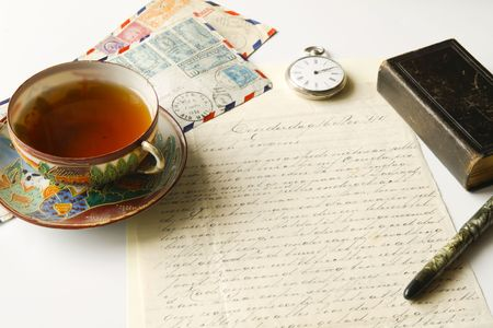 Vintage scene of old handwritten letter, us airmail envelopes, antique fountain pen, pocket watch, chinese porcelain tea cup filled with tea and lold eather pocket bible Stock Photo