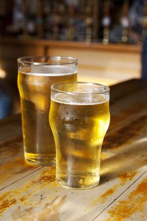 Two light golden beers on a wooden bar Stock Photo - 6676665