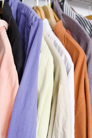 Shirts in closet on hanger in different colors photo