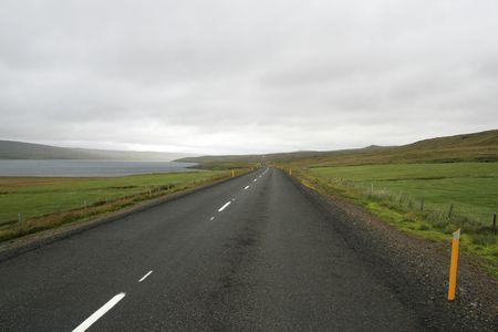 Road between lake and  bright green fields and hills in Iceland Stock Photo - 6871294