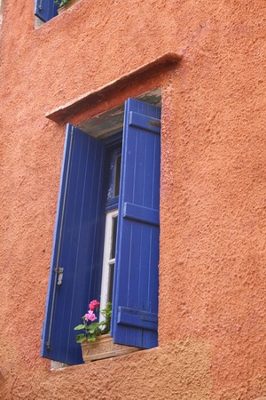 Beautiful pink wall with blue window and shutters in Crete photo