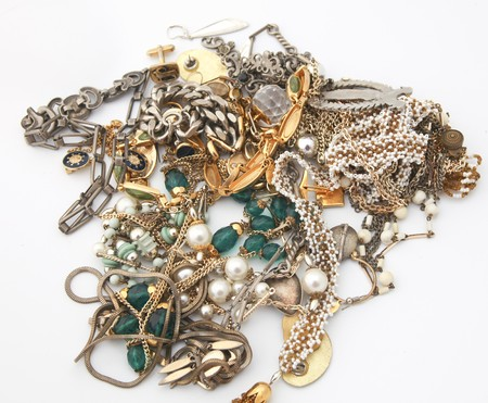 green gemstone: gold en silver jewellery on a heap