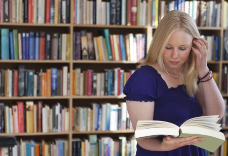 Blonde girl reading book in front of full bookshelves  photo