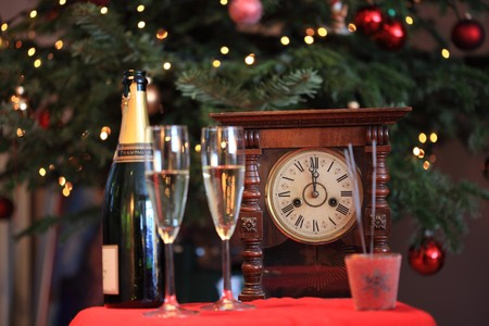 Champagne glasses and bottle in front of old fashioned clock on one minute to twelve. Focus on clock