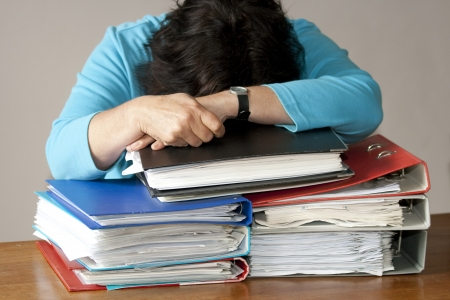 filing document: Woman resting overworked on stack of document files Stock Photo