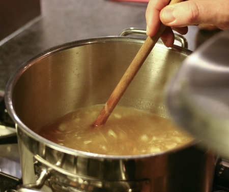 Hand with wooden ladle stirring in pan with soup Stock Photo