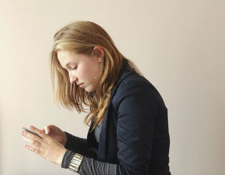 Pretty young woman using her  touch screen cell phone Stock Photo - 8143255