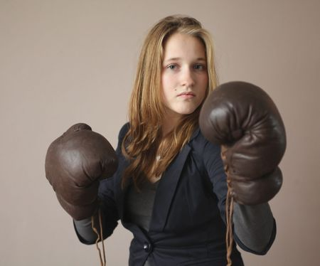 Pretty young girl with boxing gloves  looking powerful and standing tall photo
