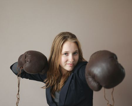 Pretty young woman with boxing gloves giving a punch. Focus on face. photo