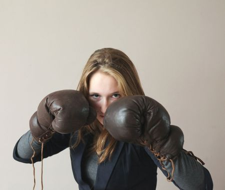 Pretty young woman with boxing gloves defending her face photo