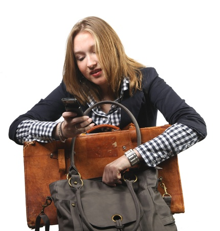 Young businesswoman with suitcase and handbag and looking at her cellphone  photo