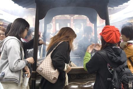 good health: TOKYO, JAPAN - APRIL 1 2009: People inhaling smoke of incense at a temple in Tokyo. It is believed this will bring good health in the new year.