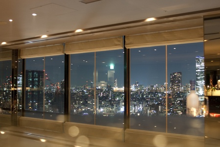JAPAN, TOKYO , APRIL 4 2009:View on Tokyo and skytower by night through windows with some reflection of the interior