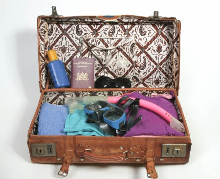 Open suitcase with beach items and passport Stock Photo