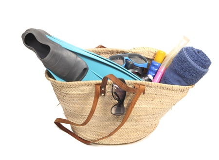 flippers: Wicker basket with towel, sunglasses, snorkel, flippers and suntan lotion Stock Photo