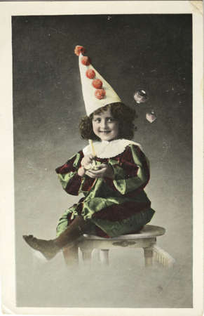 ENGLAND-CIRCA 1912: Vintage  postcard of a happy boy in costume sitting on a table blowing bubbles