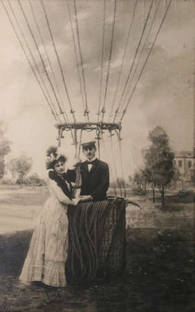 Vintage postcard from 1907 with loving couple near air balloon. Man standing proudly in basket, woman adoringly next to him.