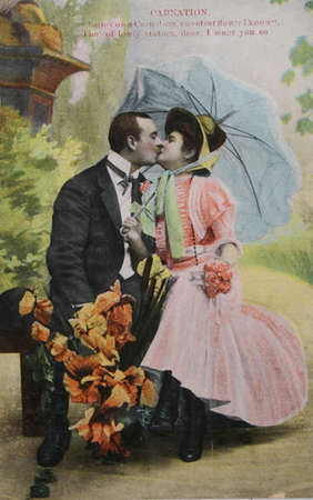Victorian romance - couple kissing under umbrella - circa 1904 vintage hand-tinted photograph Stock Photo - 9158217