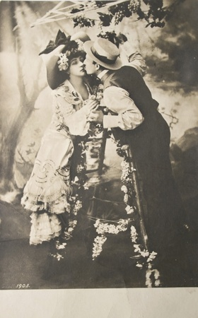 GERMANY-CIRCA 1903: Loving couple kissing iin black and white. Hand-tinted photograph postcard,circa 1903