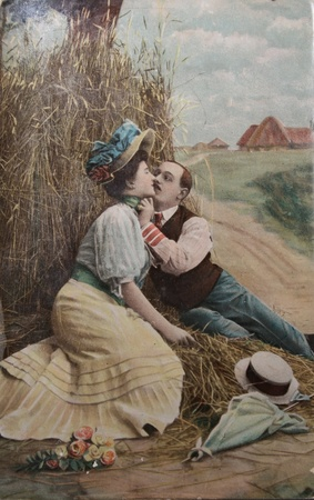 classic woman: passionate love, couple kissing in haystack- circa 1904 postcard